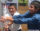 Two boys from Honduras enjoy the fresh water piped in through the new water system. USAID/Gabriella Chinchilla.