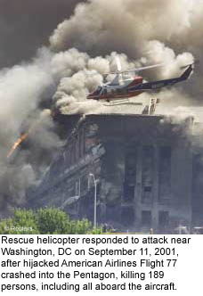 Rescue helicopter hovers over the Pentagon engulfed in smoke, while responding to attack near Washington, DC on 9/11 after hijacked American Airlines Flight 77  crashed into the Pentagon, killing 189 persons, including all aboard the aircraft.