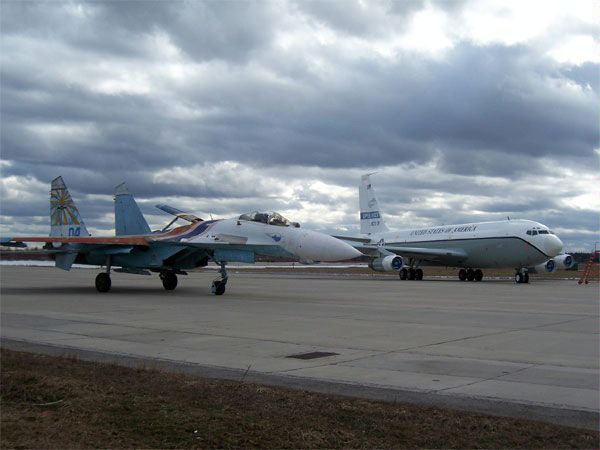 A Sukhoi Su-27 of the Russian Knights flight demo team next to a U.S. Open Skies C-135B plane, at Kubinka airbase in Russia, 16 March 2007.