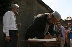 Date: 07/08/2011 Description: Imams signing guest book after walking out of the gas chamber at Auschwitz to memorialize their bearing witness and bearing the burden of that witness. - State Dept Image