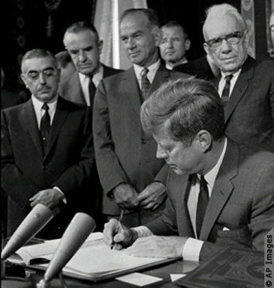 President John F. Kennedy signs the Limited Test Ban Treaty in October 1963, banning nuclear arms tests in air, in space and under water. The treaty allayed fear of the danger of atmospheric nuclear fallout.