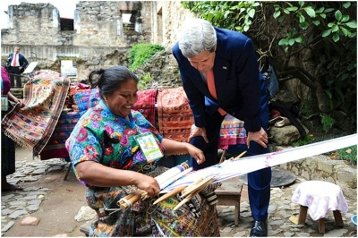 Secretary of State John Kerry examines goods made by a textile worker during a break in an Organization of American States meeting.