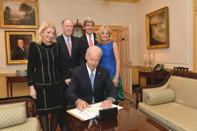 With U.S. Secretary of State John Kerry and her family looking on, Vice President Joe Biden signs the appointment papers for Catherine Russell to become the U.S. Ambassador-at-Large for Global Women's Issues at the U.S. Department of State in Washington, D.C., on January 17, 2014.