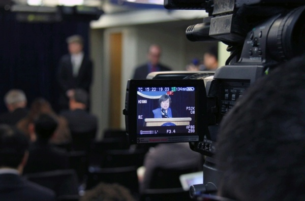 As seen from the television monitor, Under Secretary Novelli briefs the Washington Foreign Press Center on the President's Trade Agenda.