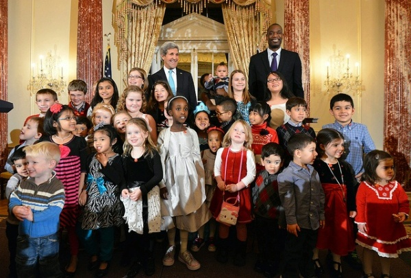 QDDR Theme: Taking care of our people; Secretary of State John Kerry and Dikembe Mutombo pose with children of State Department employees who are serving overseas at unaccompanied posts at a reception at the State Department on December 17, 2014.