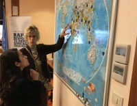 Date: 12/16/2016 Description: At the FAO, Lee shows U.S. Youth Observer Nicol Perez a map filled with blue, green and red dots. The colors correspond to her work to track infectious diseases and animals around the world. [Photo courtesy of Nicol Perez] - State Dept Image